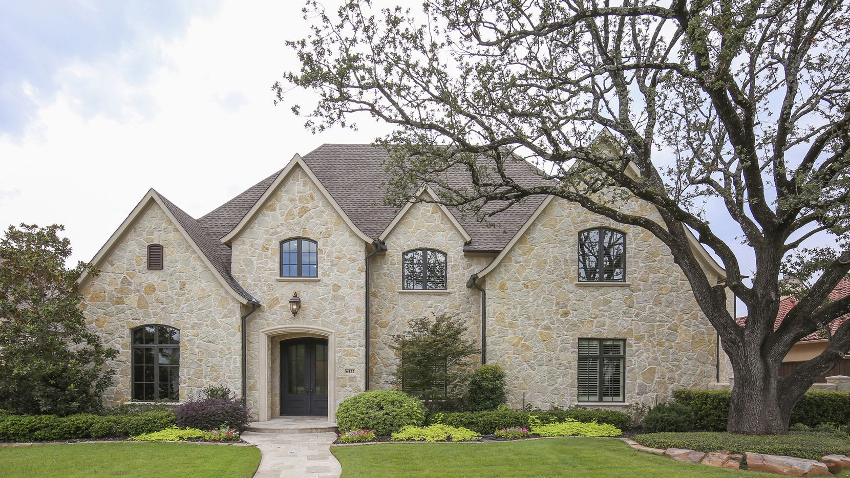 Located in Preston Hollow, the home at 6422 Stefani Drive features a pool, spa, loggia, outdoor fireplace and covered patio.