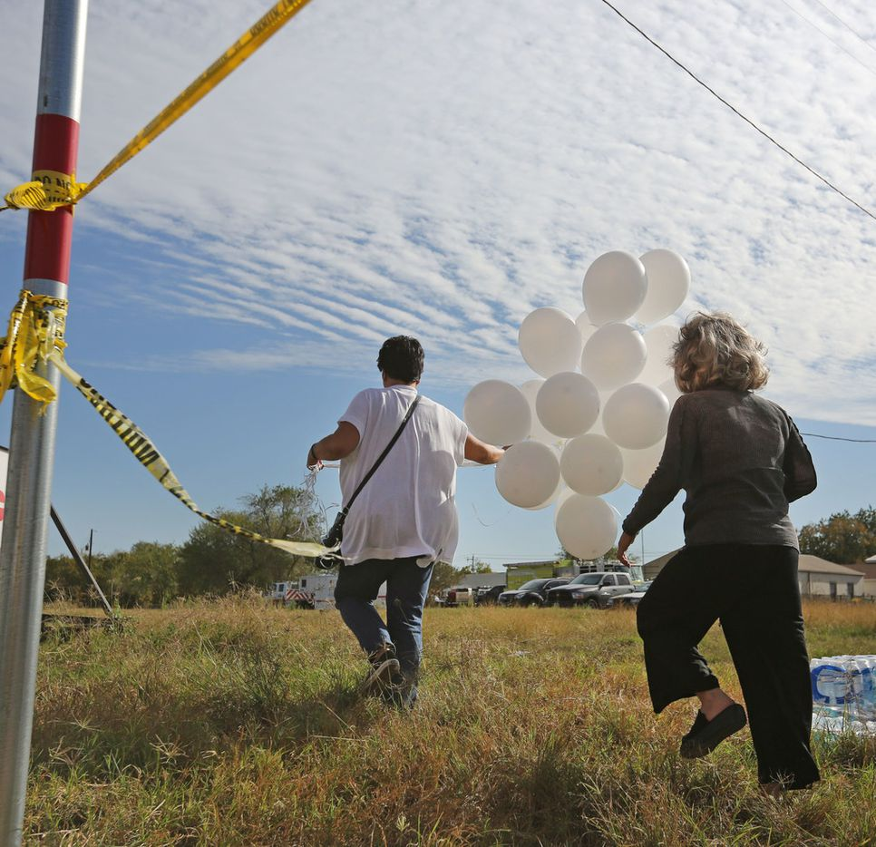 Michelle Trigo, left and Malinda Lamford of San Antionio deliver 26 balloons, flowers, and a stuffed teddy bear to the First Baptist Church of Sutherland Springs in Sutherland Springs, Texas. At least 26 people died Sunday after a gunman opened fire at a Baptist church in the small town southeast of San Antonio. Photographed on Monday, November 6, 2017. (Louis DeLuca/The Dallas Morning News)