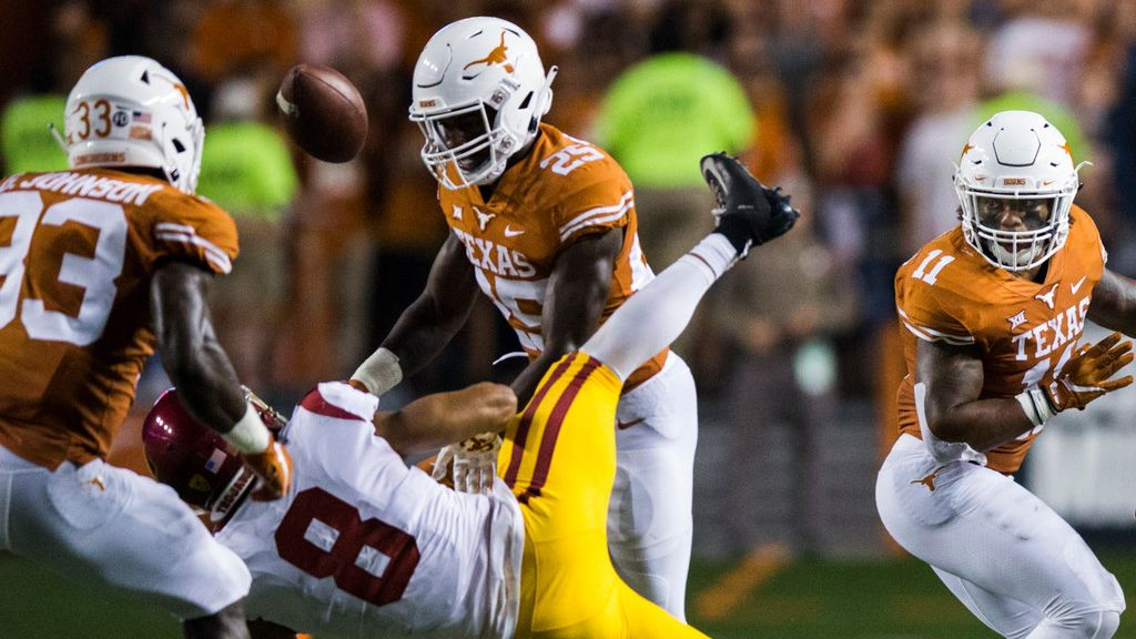 Texas Longhorns defensive back B.J. Foster (25) tackles USC Trojans wide receiver Amon-Ra St. Brown (8), causing a fumble during the fourth quarter of an NCAA football game between the Texas Longhorns and the USC Trojans on Saturday, September 15, 2018 at Darrell K Royal Memorial Stadium in Austin, Texas. A penalty was called on Foster for targeting the receiver. (Ashley Landis/The Dallas Morning News)