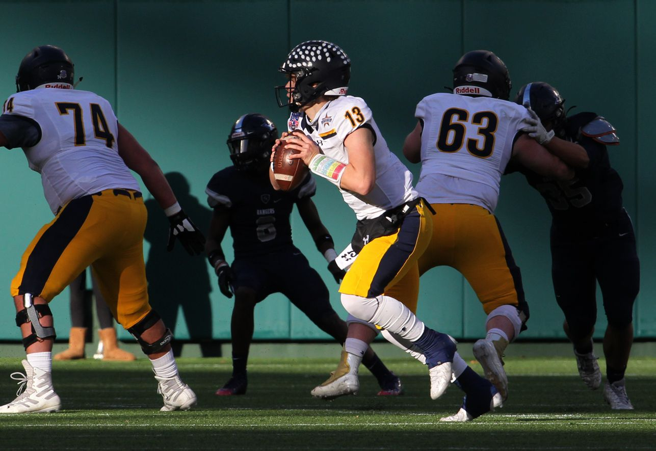 Highland Park quarterback Brayden Schager (13) rolls out behind the protection of his offensive line in search of an open receiver during second quarter action against Frisco Lone Star. The two teams played their Class 5A Division l Region ll semifinal football playoff game held at Globe Life Park in Arlington on December 24, 2020. (Steve Hamm/ Special Contributor)