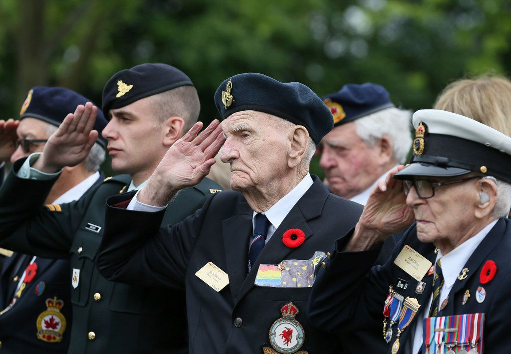 Canadian World War II veteran Dick Brown (second from right) and Rod Deon (right) salute as they attend a ceremony at the Beny-sur-Mer Canadian War Cemetery in Reviers, Normandy, France, Wednesday, June 5, 2019. A ceremony was held on Wednesday for Canadians who fought and died on the beaches and in the bitter bridgehead battles of Normandy during World War II.