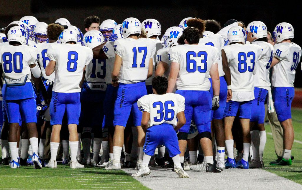Plano West receiver Ricardo Benitez (36) peers into a huddle of his teammates. Benitez is only four foot, two inches tall because he was born without femurs in either leg. He plays receiver and is shown before the start of a high school football game against Wylie at Wylie ISD Stadium in Wylie, Friday, October 13, 2017.