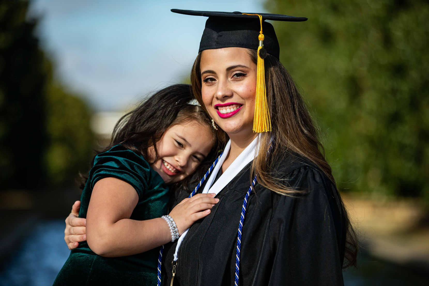 Itzel Ramirez Tapia poses with her cap and gown with her daughter Samantha Tapia, 5, at UTD. Ramirez is a first-generation college student who will graduate this semester with a bachelor's in computer science in Richardson on Wednesday, December 16, 2020. (Lola Gomez/The Dallas Morning News)