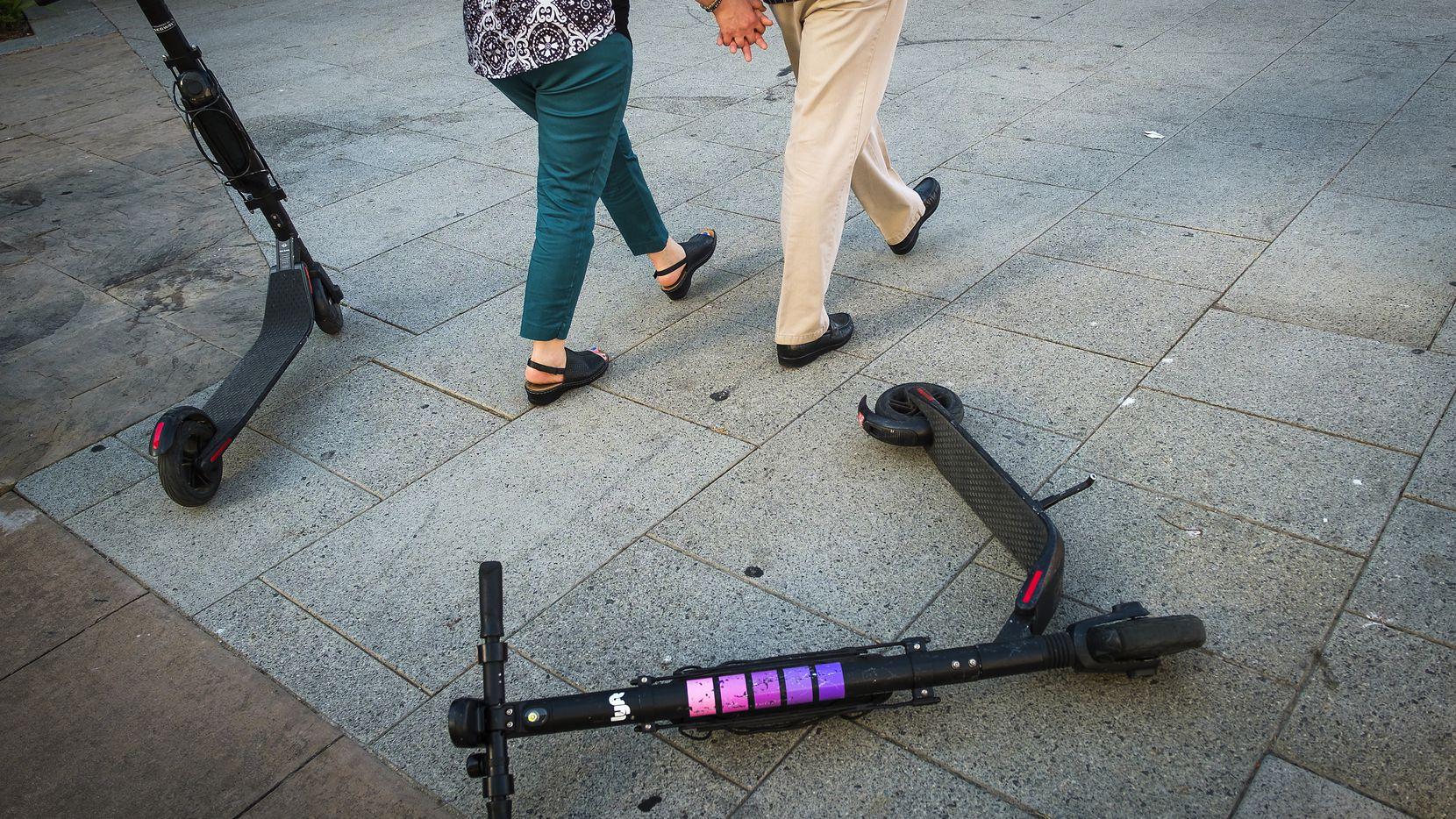 A Lyft scooter lies on a sidewalk along Commerce Street in downtown Dallas.