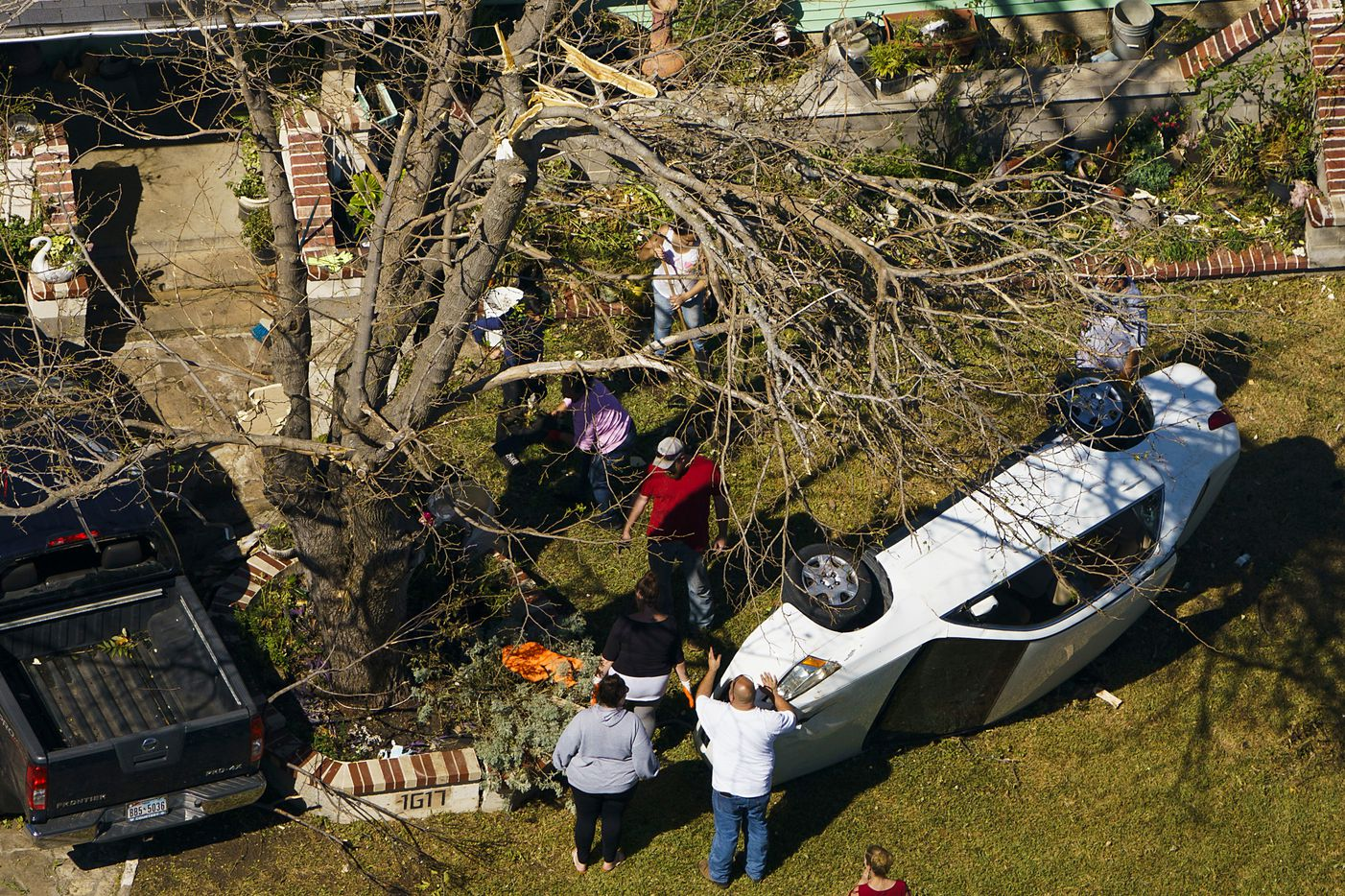 People survey an upturned automobile in the front yard of a home on Monday, Oct. 21, 2019, in Garland.