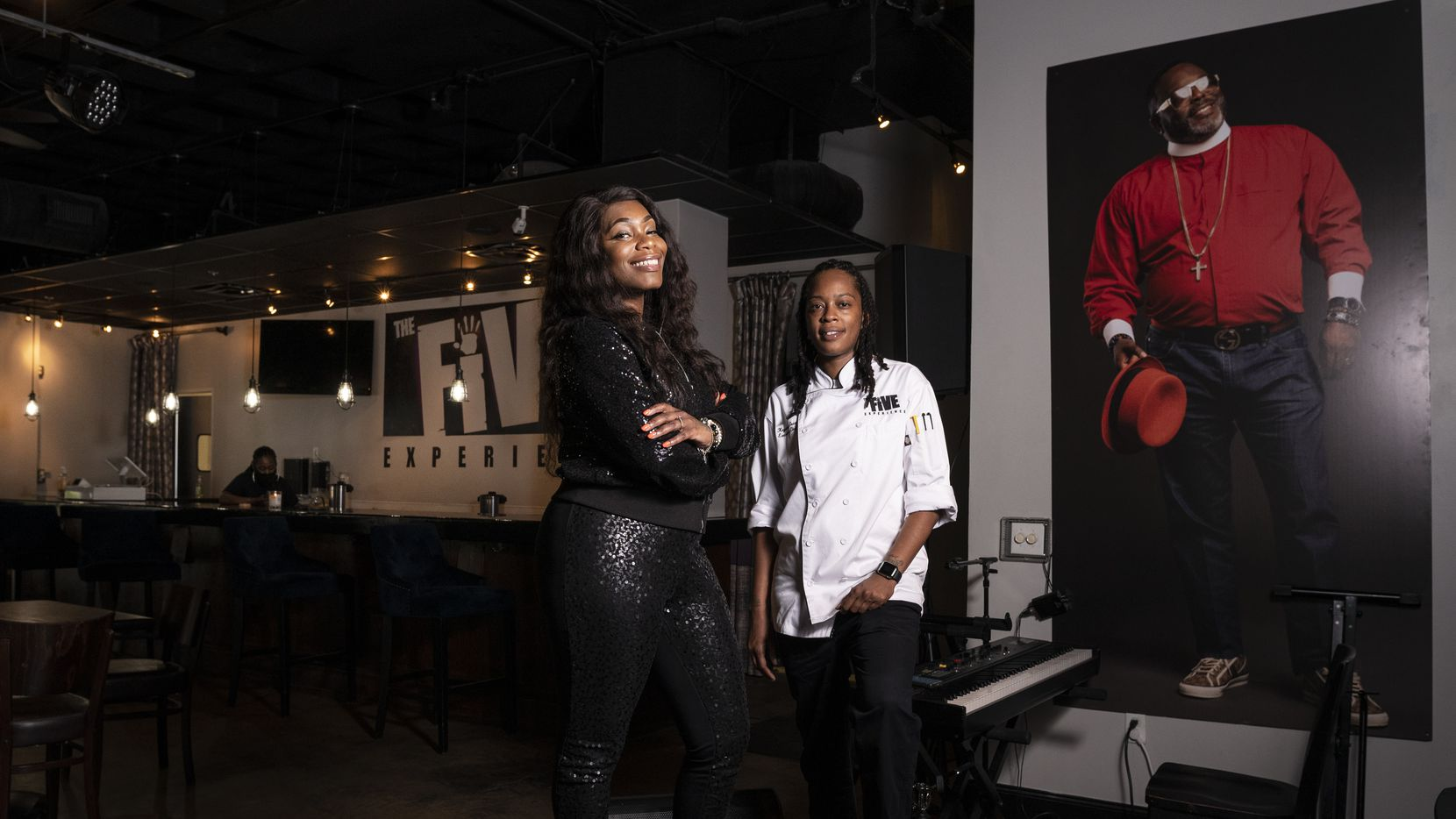 Owner Fayth Jefferson, left, and executive chef Keyonna Grant stand by a photo of the late Bishop Omar Mulidna Jahwar at The Five Experience. The restaurant opens in May 2021 on Botham Jean Boulevard in Dallas.