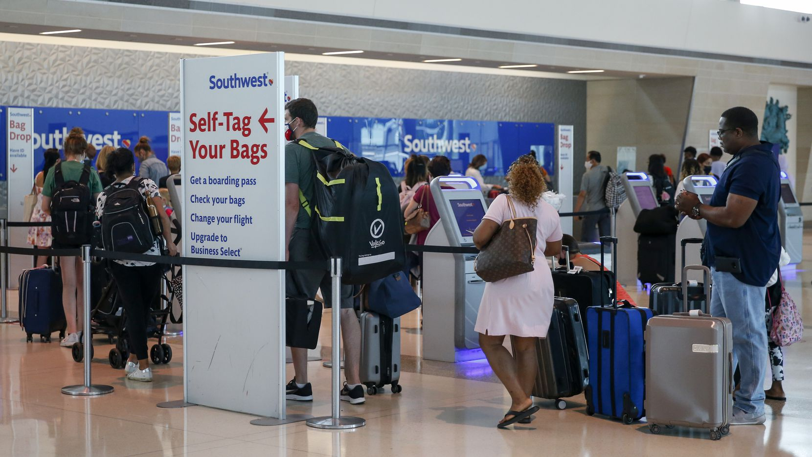 Airline passengers waited to check baggage at a Southwest ticket counter at Dallas Love Field on June 18.