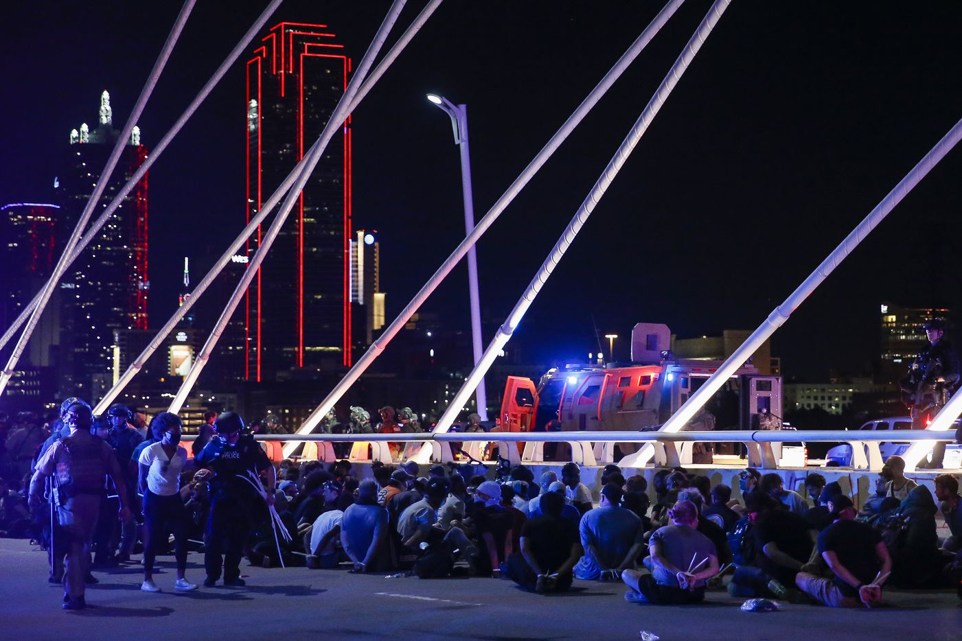 Police surround and detain hundreds of protesters who marched onto the Margaret Hunt Hill Bridge while demonstrating against police brutality on Monday, June 1, 2020, in Dallas. The protesters were transported to the Dallas County Jail where they were later released.