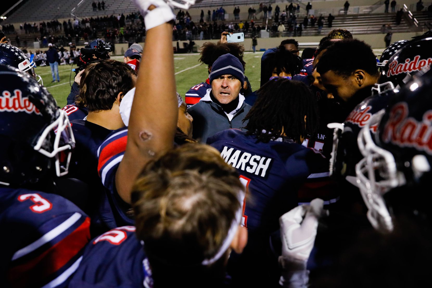 Denton Ryan football coach Dave Henigan celebrates with his players after winning the District 5-5A Division I title against Frisco Lone Star at the C.H. Collins Complex in Denton on Thursday, Dec. 4, 2020. Denton Ryan won, 35-21. (Juan Figueroa/ The Dallas Morning News)