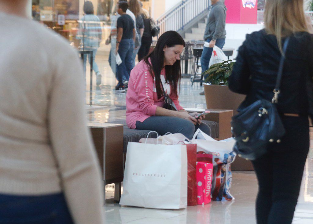 Melissa Darter waits for her sister after shopping at Stonebriar Centre in Frisco, Texas Black Friday morning November 24, 2017. They drove from Ardmore, OK. to shop at the Collin County shopping mall.