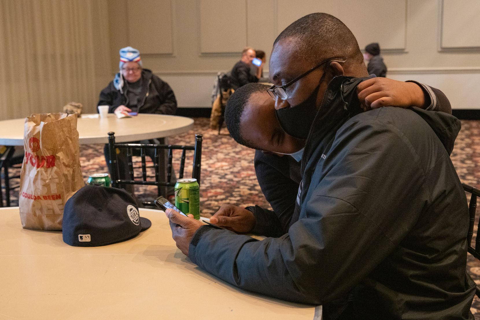 """Chidi Anorue, 8, gives dad Patrick Anorue a hug at the warming center located at Ruthe Jackson Center in Grand Prairie. The Anorues came to the center yesterday after their home lost power and were unable to find a hotel. """"Thank God we have this,"""" Patrick said."""