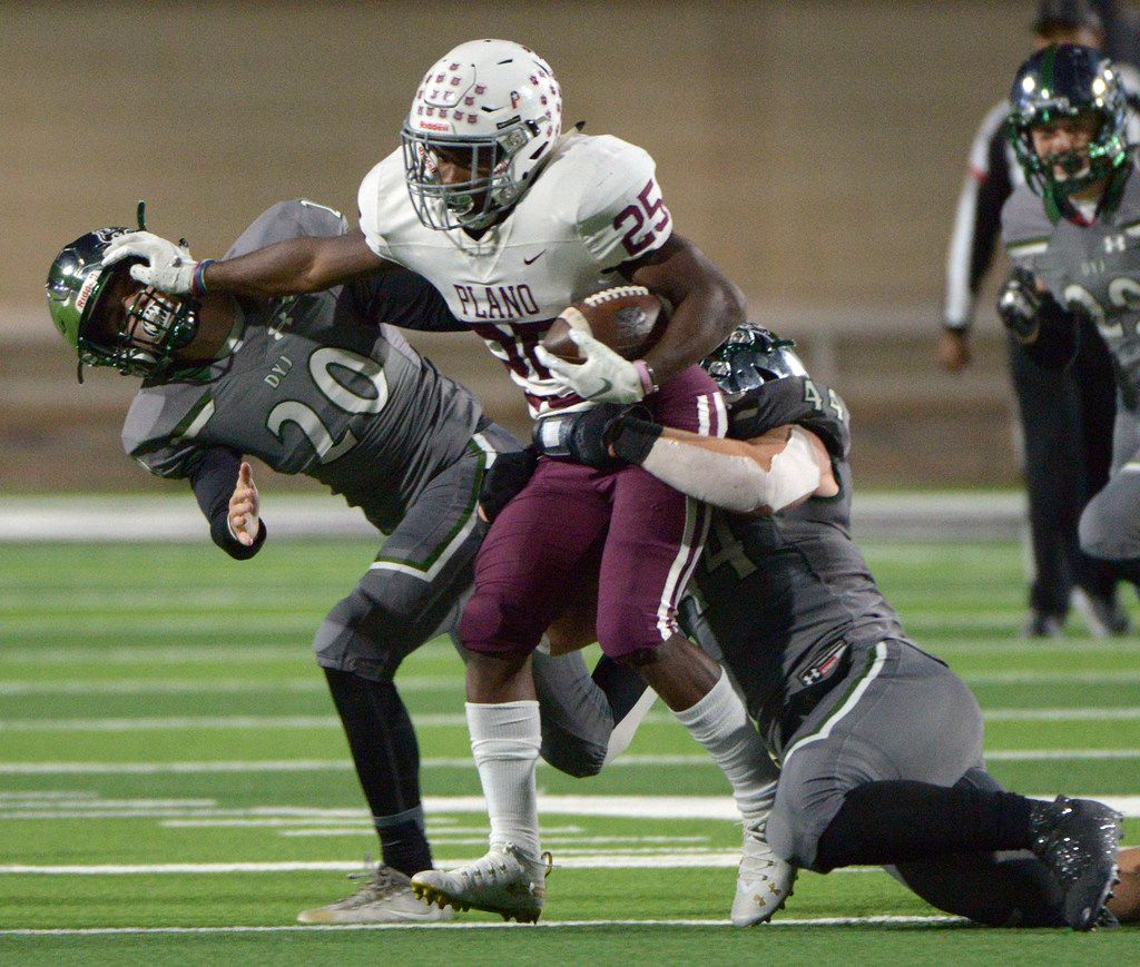 Plano's Tylan Hines tries to run through the tackle attempts by Prosper's Will Schreve (20) and Aidan Siano (44) in the first half of a high school football game in Prosper, Texas, Friday, Nov. 8, 2019. (Matt Strasen/Special Contributor)