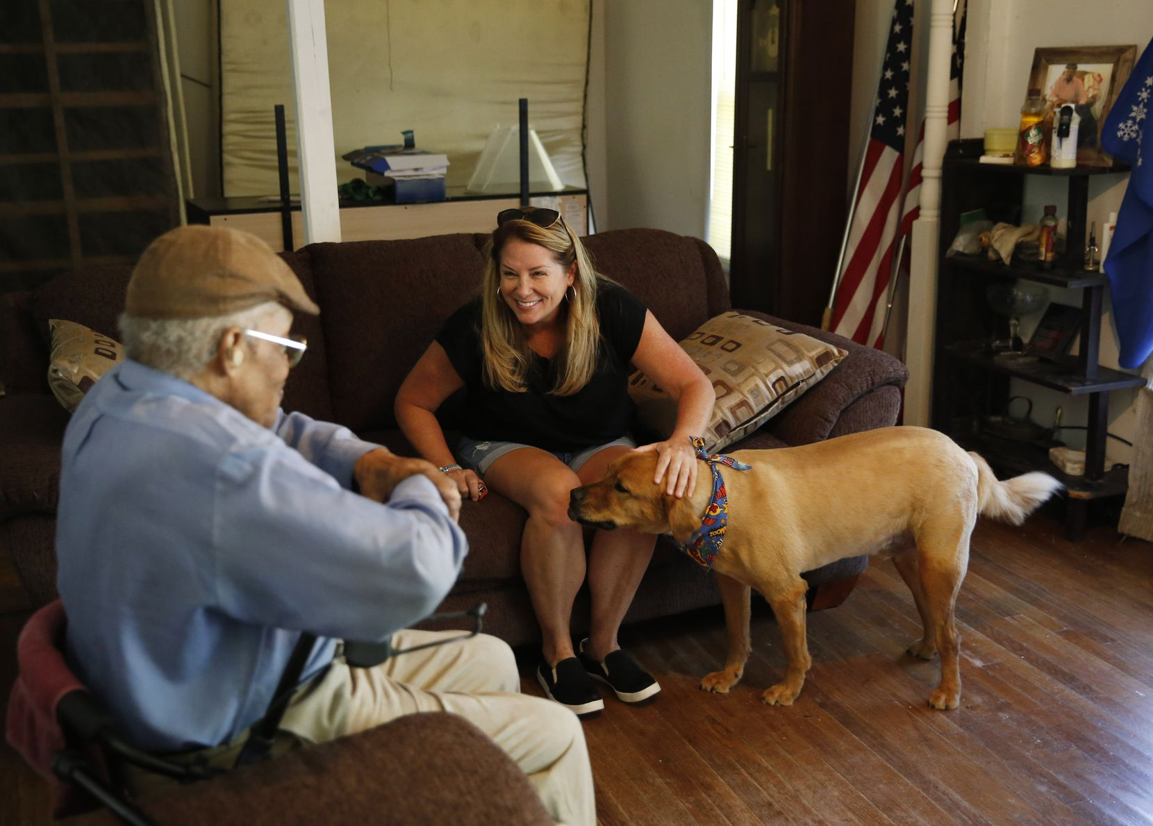 James Evans, 83, talks with Jeanne Marie Boyne (right), a volunteer for the Senior Pet Assistance Network as she pets Renny at his home in Dallas, on Saturday, July 13, 2019.
