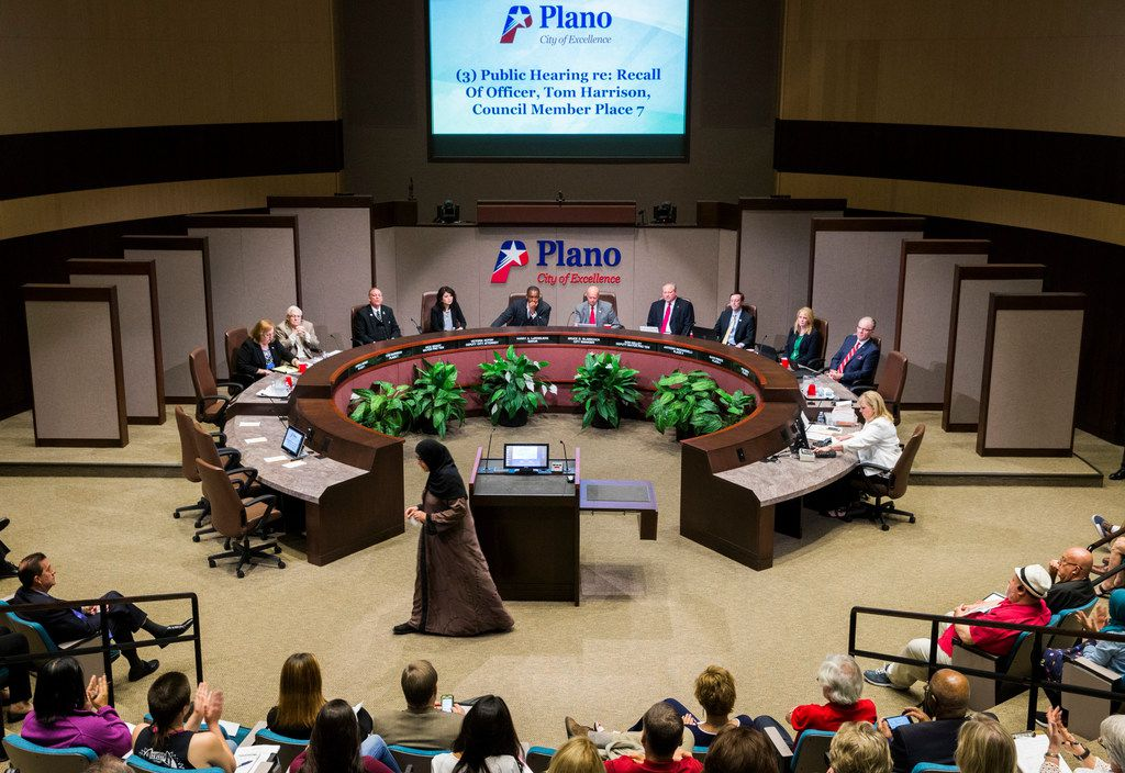 Plano resident Zeba Siddiqui walks away from the podium after speaking against Plano City Council member Tom Harrison (second from left) during a hearing in which Harrison defended his post on social media about banning Islam in public schools in April.