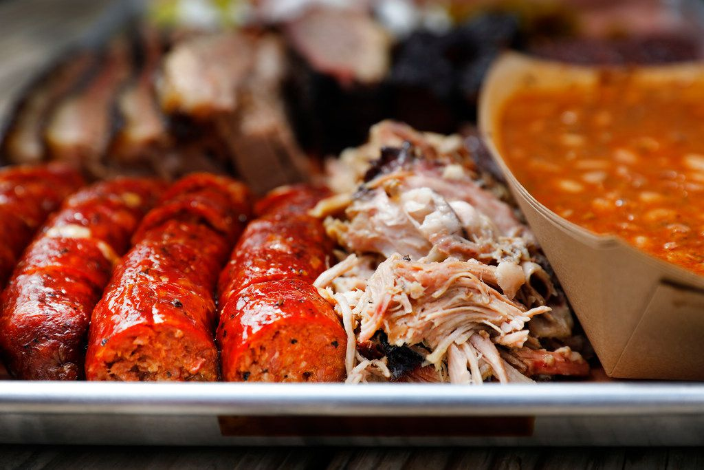 A tray of jalapeño and cheese sausage, pulled pork, beans, brisket and burnt ends is served at Guess Family Barbecue in Waco.