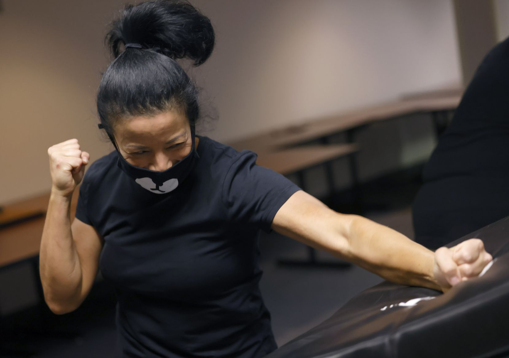 United Airlines flight attendant Elaine Lackland practices self-defense measures with a combat training pad.