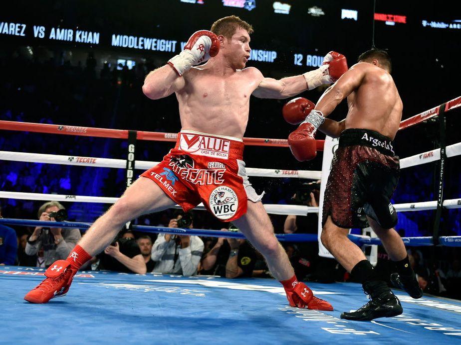 El campeón mexicano Saúl Canelo Alvarez (izq) golpea a Amir Khan durante su pelea del 7 de mayo de 2016 en el T-Mobile Arena de Las Vegas.