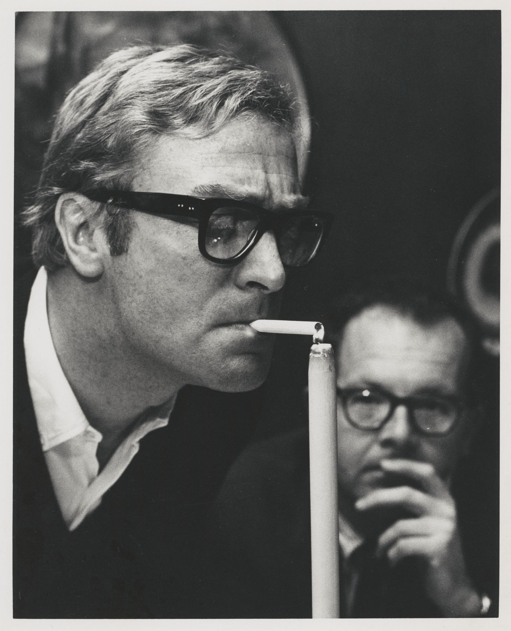 """Actor Michael Caine lights a cigarette using a candle, circa 1970s. The photo is included in the exhibit, """"Andy Hanson: Picturing Dallas, 1960-2008, on display at the in the Fondren Library at SMU, through Jan. 29, 2020. Using photos from Hanson's vast photographic archive, held by the DeGolyer Library at SMU the show celebrates Hanson's long career in Dallas, where he was a staff photographer for the Dallas Times Herald -- and later an independent photographer -- covering society, politics, the performing arts, and major news events of the day."""