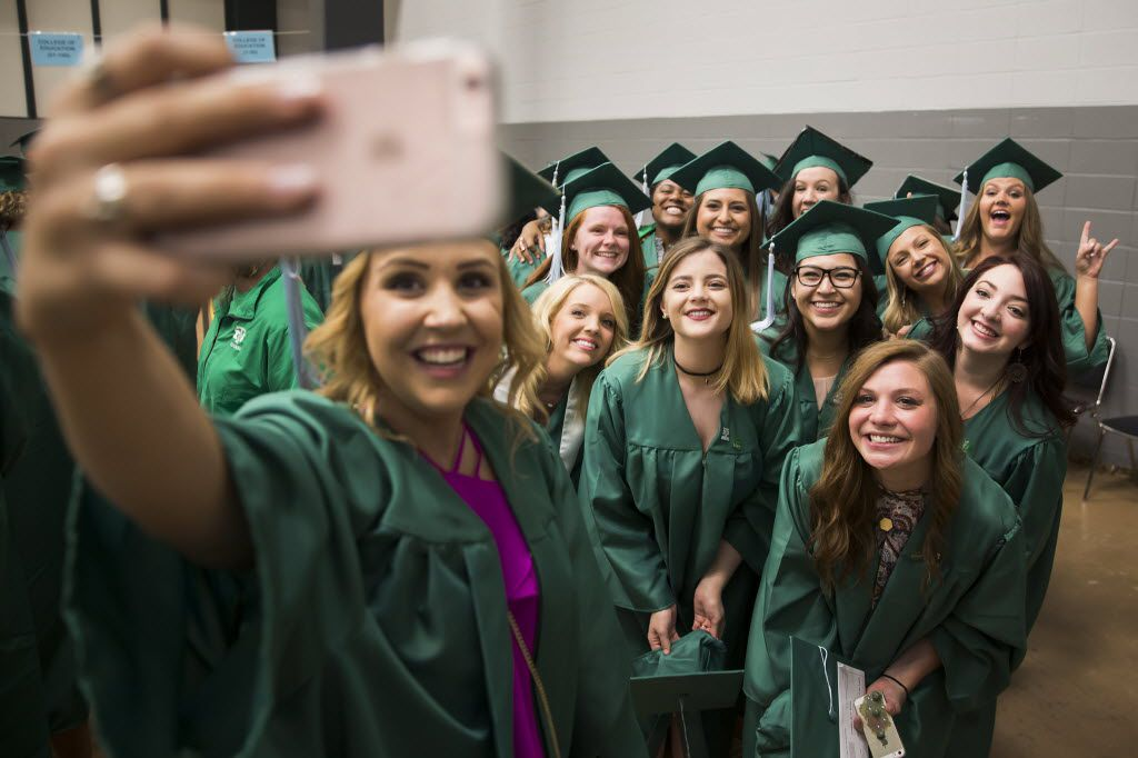 Katelynn Blasavage (center) poses for a selfie with fellow UNT graduates before they process into the coliseum for graduation on May 14, 2016, in Denton.