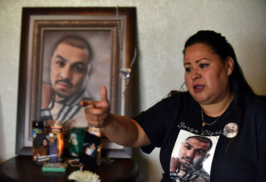 Vanessa Olguin makes the hand signal for a gun while speaking about her husband's death. Jorge Olguin was shot at a children's birthday after an argument with an apartment complex security guard.