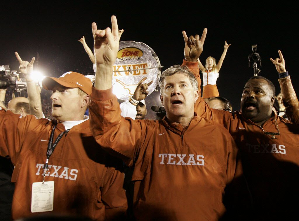 FILE - In this Jan. 4, 2006, file photo, Texas head coach Mack Brown, center, does the hook'em horns sign with the coaching staff after they beat Southern California 41-38 in the Rose Bowl, the national championship college football game, in Pasadena, Calif. (AP Photo/Kevork Djansezian, File)