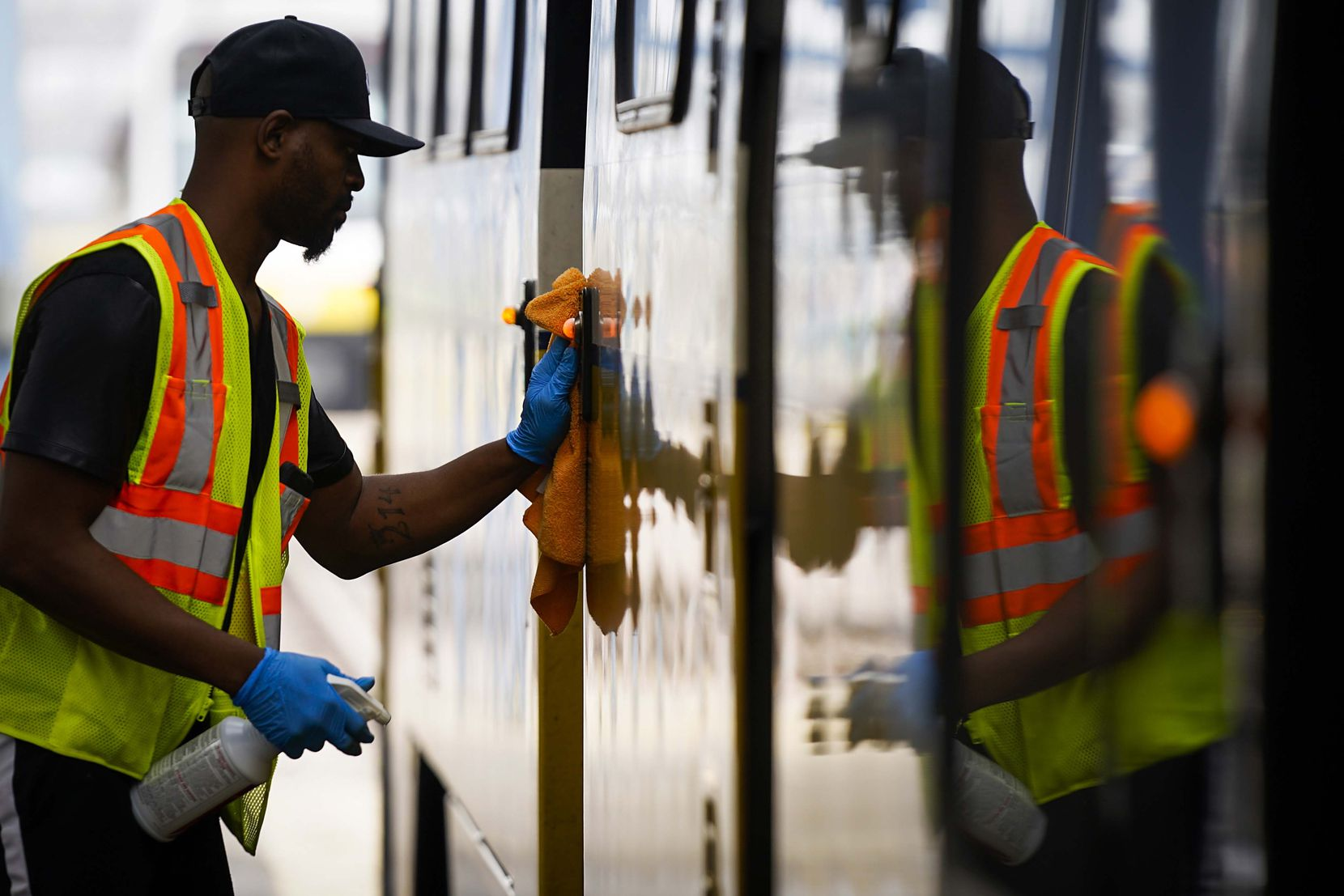 Michael Beck wipes down push buttons with disinfectant as he cleans a DART rail train at the the transit authority's Central Rail Operating Facility on Tuesday, March 17, 2020, in Dallas. Due to coronavirus concerns, the once-daily regular cleaning of the trains has been increased to three times per day, with particular emphasis on high touch areas.