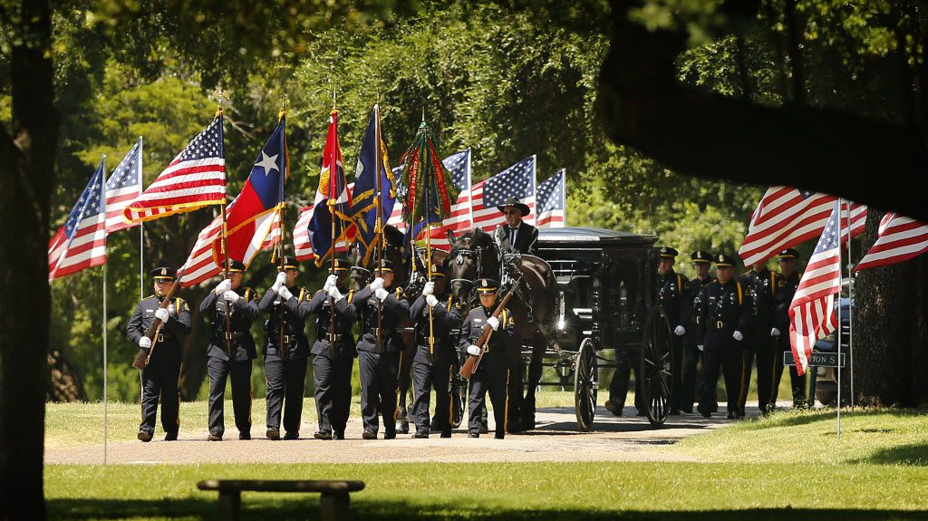 The horse-drawn caisson with the flag-draped casket of  Dallas police Sgt. Michael Smith follows the color guard to the graveside as Smith was laid to rest at the Restland Funeral Home and Cemetery in Dallas, Thursday, July 14, 2016. Smith was gunned down in an ambush attack in downtown Dallas a week ago. Four Dallas police officers and one DART officer were killed. (Tom Fox/The Dallas Morning News)