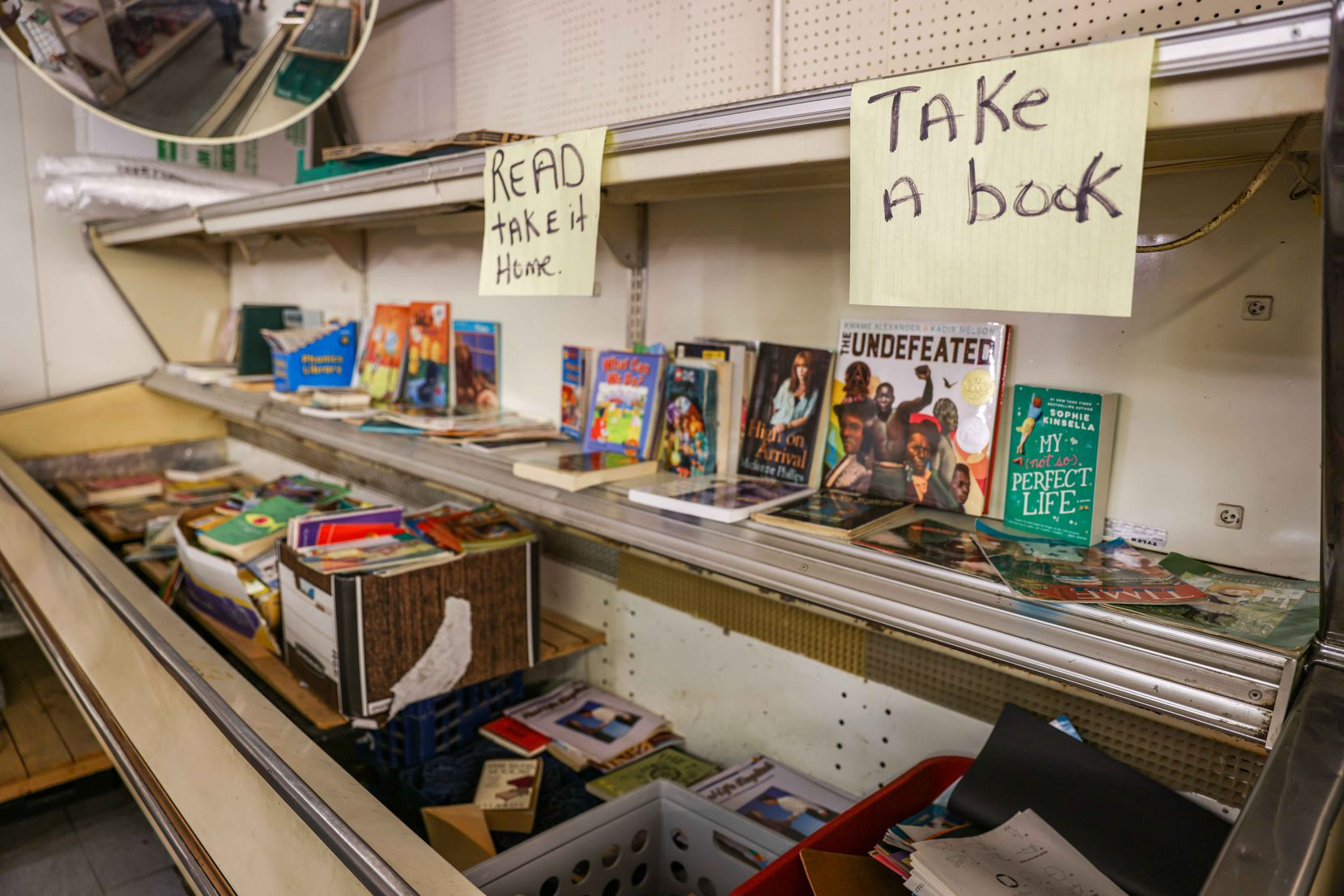 Books donated to the community rest in an old, repurposed refrigerator inside Allen's, a grocery store in South Dallas.
