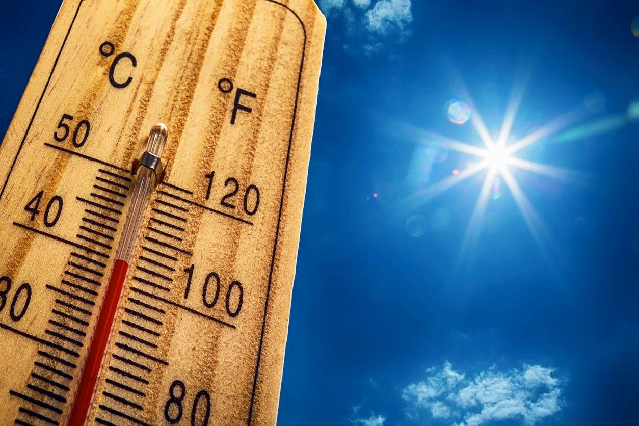 Un termómetro registra temperaturas arriba de los 100 grados fahrenheit en un día con sol.