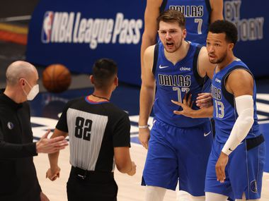 Dallas Mavericks guard Luka Doncic (77) questions a call from referee Suyash Mehta (82) as Dallas Mavericks guard Jalen Brunson (13) restrains him in a game against the Golden State Warriors during the third quarter of play at American Airlines Center on Wednesday, February 4, 2021in Dallas.