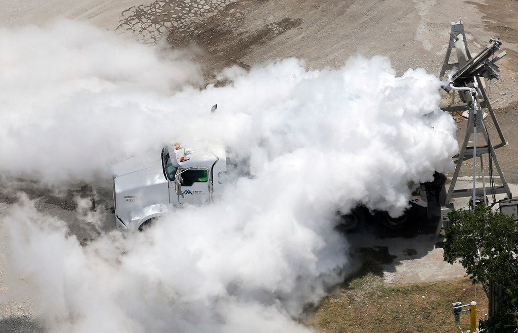 A mixture of nitrogen gas and water vapor engulfs a truck at the Martin Marietta plant after liquid nitrogen is inserted into the concrete truck to cool the load on Friday in McKinney. (Vernon Bryant/Staff Photographer)