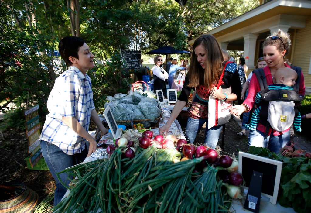 Megan Neubauer of Pure Land Organic, left, sells produce to Liz Lamb, center, and Amanda Phillips, right, carrying 9-month-old Maddock at the McKinney Farmer's Market.