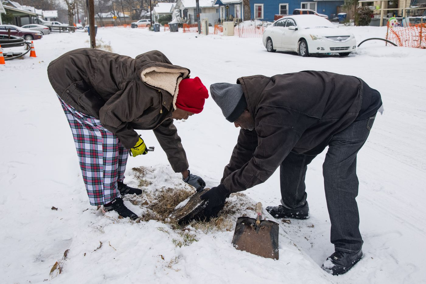 Patricia Broadway (left) and Leon Morris put the cover back after shutting the water off in Broadway's home in east Dallas on Wednesday, Feb. 17, 2021. Broadway noticed a pipe busted under her kitchen even though she said she did everything right.