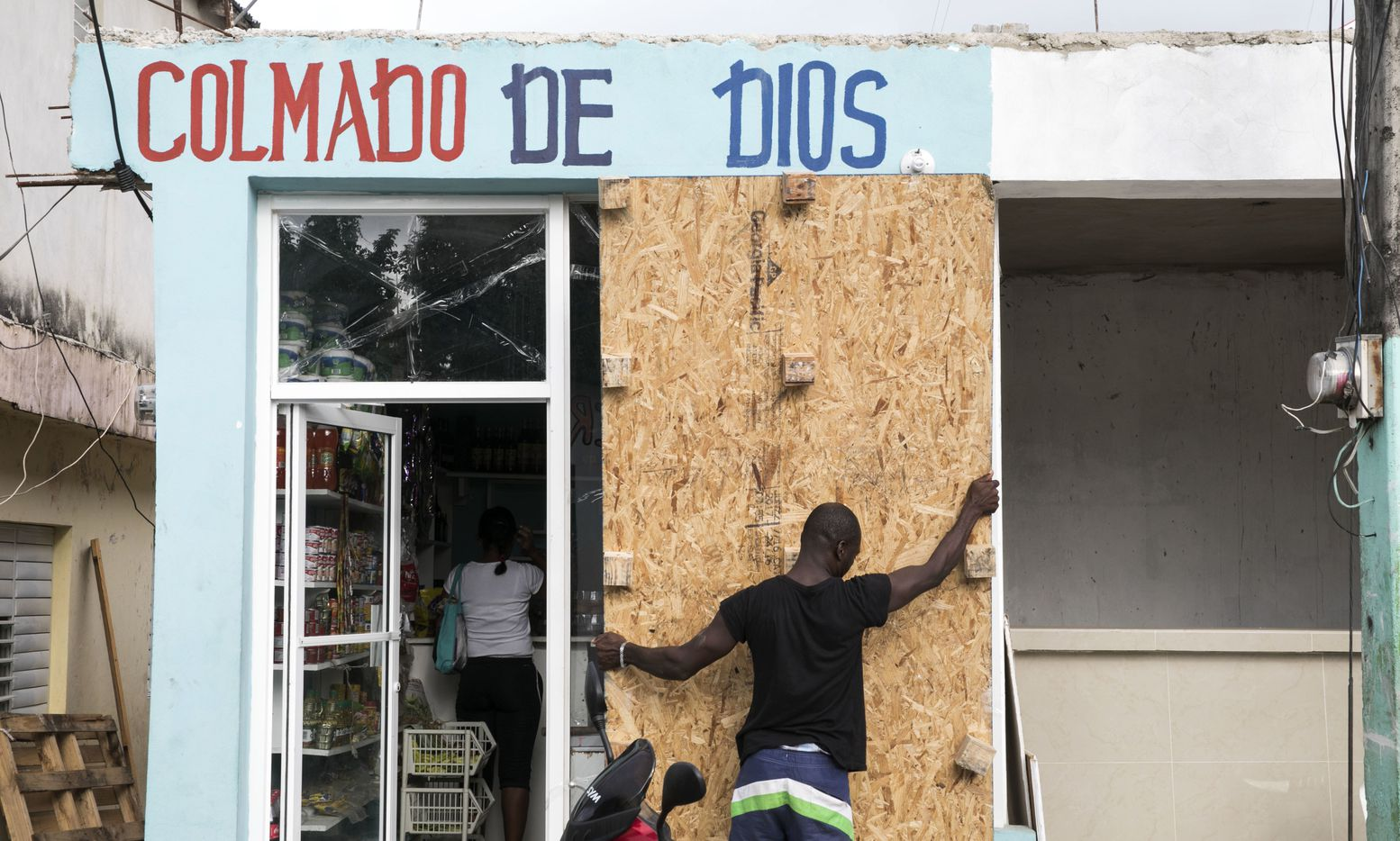 A man covers a bodega's windows before the arrival of Hurricane Irma in Las Terrenas, Dominican Republic, on Wednesday.