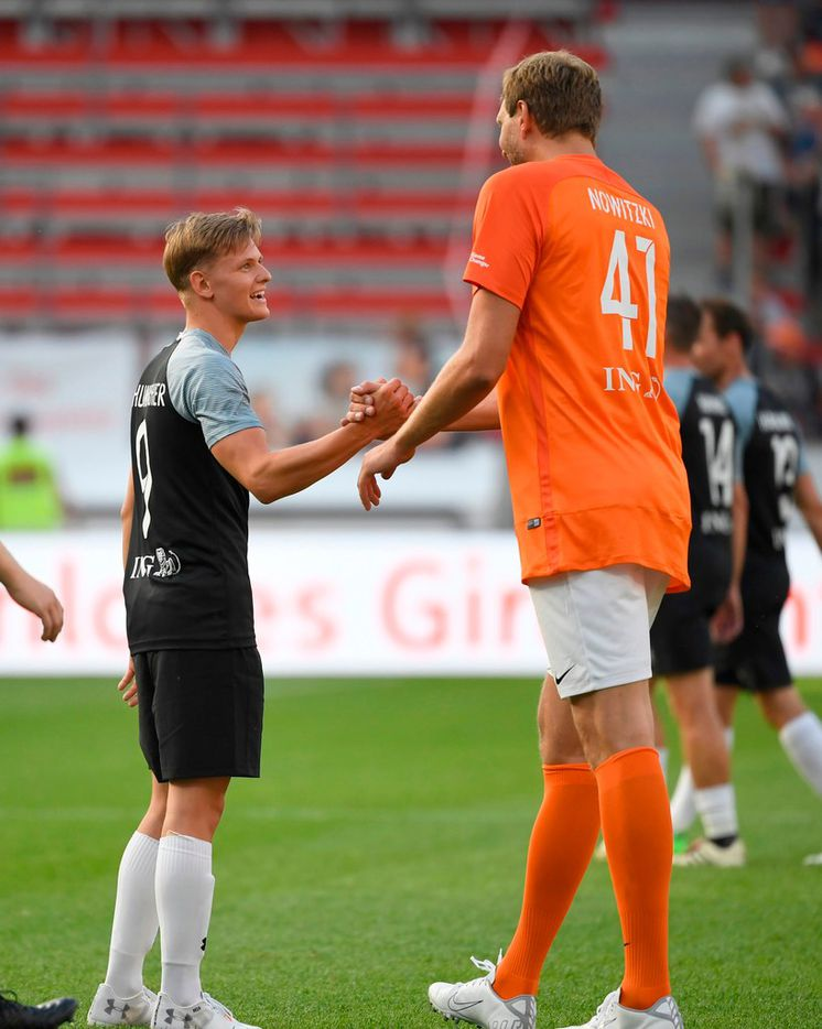 "Mick Schumacher and Dirk Nowitzki of Nowitzki All Stars shake hands during the ""Champions for Charity"" friendly football match at Bay Arena on July 21, 2019 in Leverkusen, western Germany. (Photo by INA FASSBENDER / AFP)INA FASSBENDER/AFP/Getty Images"