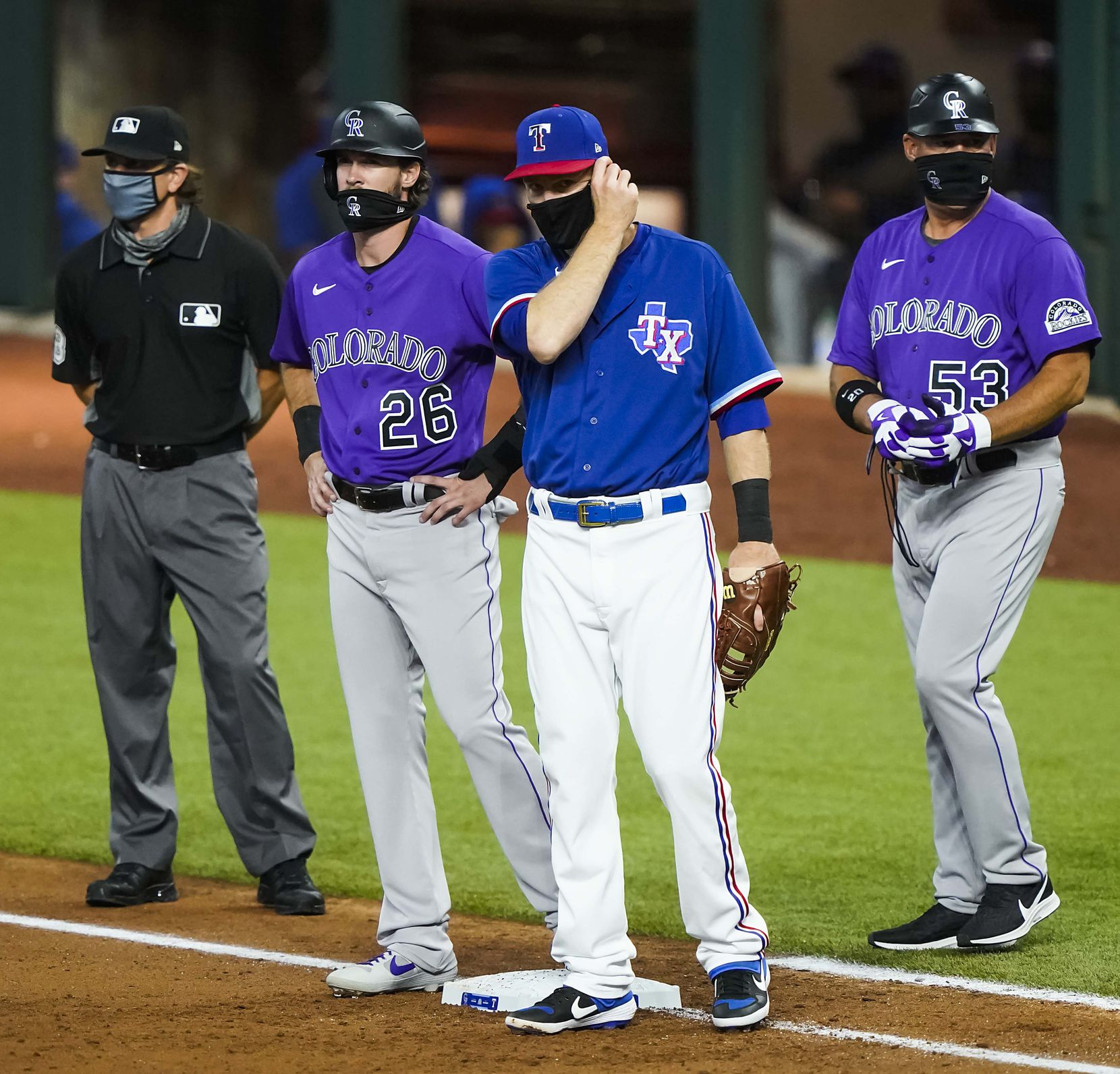 Texas Rangers first baseman Todd Frazier adjusts his face mask as umpire Chris Guccione, Colorado Rockies outfield David Dahl and first base coach Ronnie Gideon all wear theirs during the first inning of an exhibition game at Globe Life Field on Tuesday, July 21, 2020.