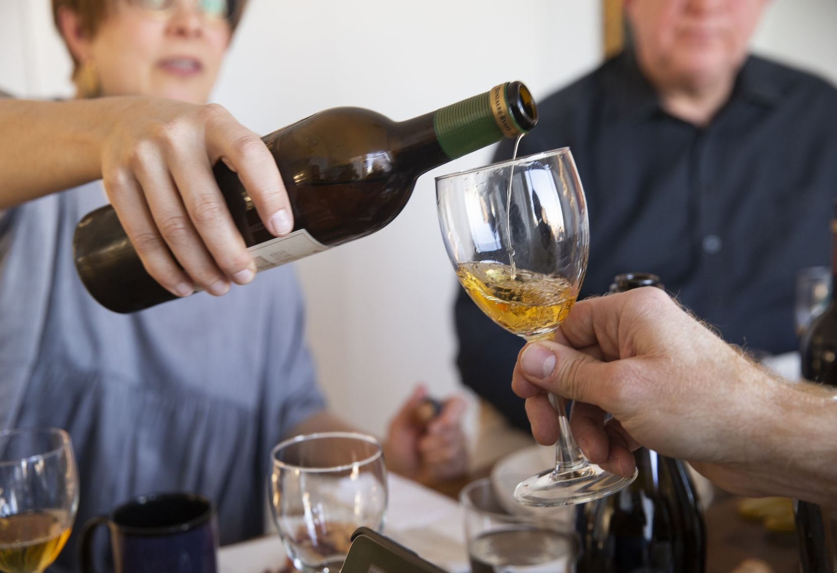 """Jennifer Uygur pours James Tidwell a glass of the González Byass """"Viña AB"""" Amontillado Seco during The Dallas Morning News Wine Panel's tasting of various wines to go with jamón ibérico from Enrique Tomas in February."""