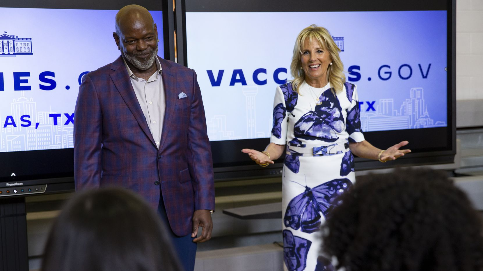 Dallas Cowboys legend Emmitt Smith (left) and first lady Jill Biden speak to people in the observation area on June 29, 2021, during a tour of the vaccination site at Emmett J. Conrad High School in Dallas.