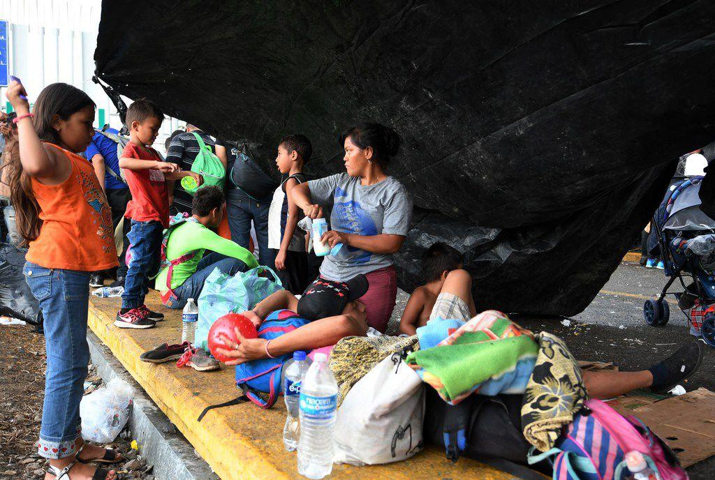 Honduran migrants heading in a caravan to the U.S. wait to cross the border from Ciudad Tecun Uman, Guatemala, to Ciudad Hidalgo, Mexico, on Oct. 21, 2018.