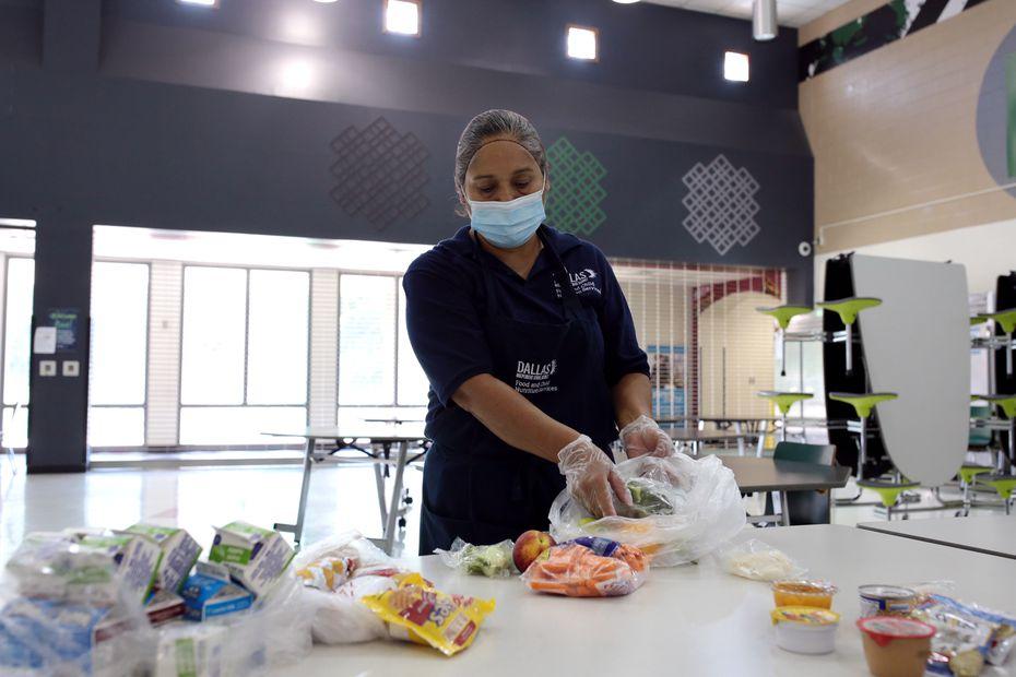 María Lorena Trejo prepara los paquetes de comida que serán entregados más tarde a las familias de los estudiantes del DISD.