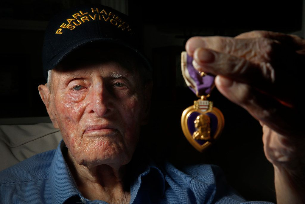 Pearl Harbor survivor John E. Lowe holds his Purple Heart at his son's house in Arlington. He is one of the few remaining North Texas-based survivors of the attack on Pearl Harbor. (Jae S. Lee/Staff Photographer)