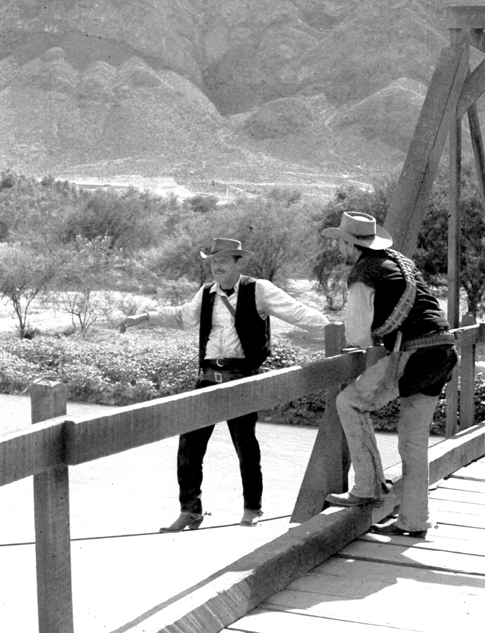Off-camera and behind-the-scenes, actor William Holden (left) plays daredevil by tightrope-walking a support cable for the bridge that will be blown up in the movie The Wild Bunch.