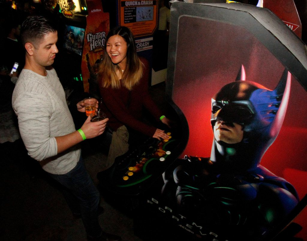 Tiffany Chen reacts to her score as her date, Michael Smith, handles the glasses of cider as the couple enjoy the atmosphere at Cidercade.