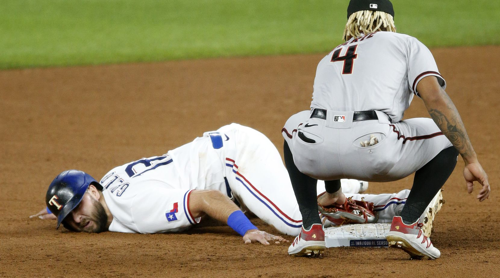 Texas Rangers right fielder Joey Gallo (13) steals second base as Arizona Diamondbacks second baseman Ketel Marte (4) is late with the tag  during the second inning at Globe Life Field in Arlington, Texas, Tuesday, July 28, 2020. Though he slid awkwardly into the dirt, Gallo was able to hold his foot on the base. (Tom Fox/The Dallas Morning News)