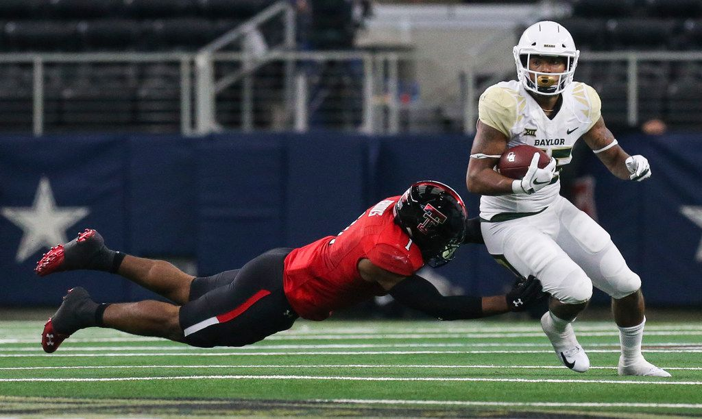Texas Tech Red Raiders linebacker Jordyn Brooks (1) attempts to bring down Baylor Bears running back Trestan Ebner (25) during the first half a matchup between Baylor and Texas Tech on Saturday, Nov. 24, 2018 at AT&T Stadium in Arlington, Texas. (Ryan Michalesko/The Dallas Morning News)