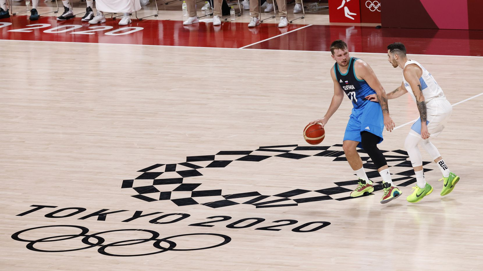 Slovenia's Luka Doncic (77) brings the ball up the court as Argentina's Luca Vildoza (17) defends in the second half of play during the postponed 2020 Tokyo Olympics at Saitama Super Arena on Monday, July 26, 2021, in Saitama, Japan.
