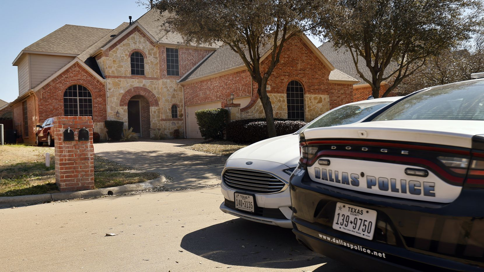 A pair of Dallas Police cars parked outside the home of Dallas officer Bryan Riser in south Grand Prairie, Texas, Thursday, March 4, 2021.