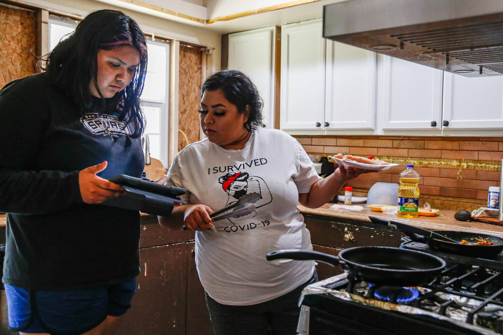 Veloz's sister, 15-year-old Kimberly Veloz, shows her something on an iPad while Veloz prepares food in the kitchen.