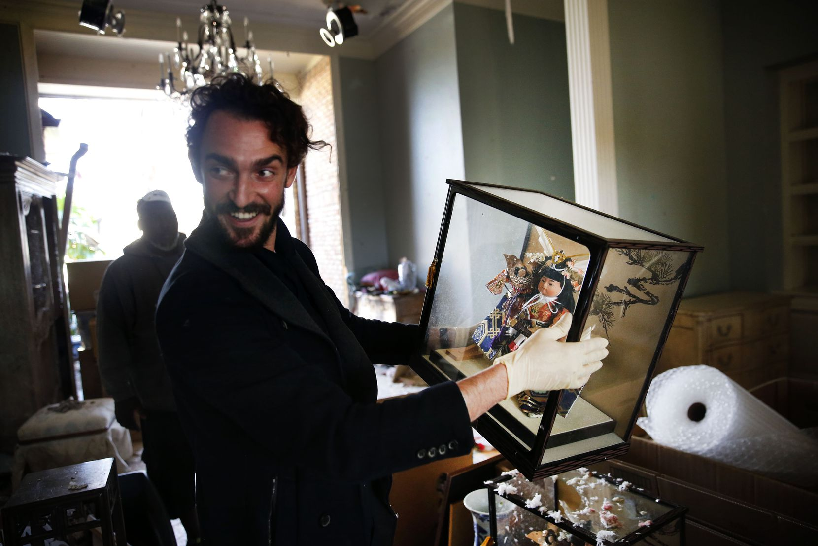 Joshua von Ammon of ART of Dallas-Fort Worth, an art recovery and restoration company, is surprised how the Asian dolls were undamaged in Brenda Schneider's Preston Hollow neighborhood home in Dallas, Tuesday, Oct. 22, 2019.