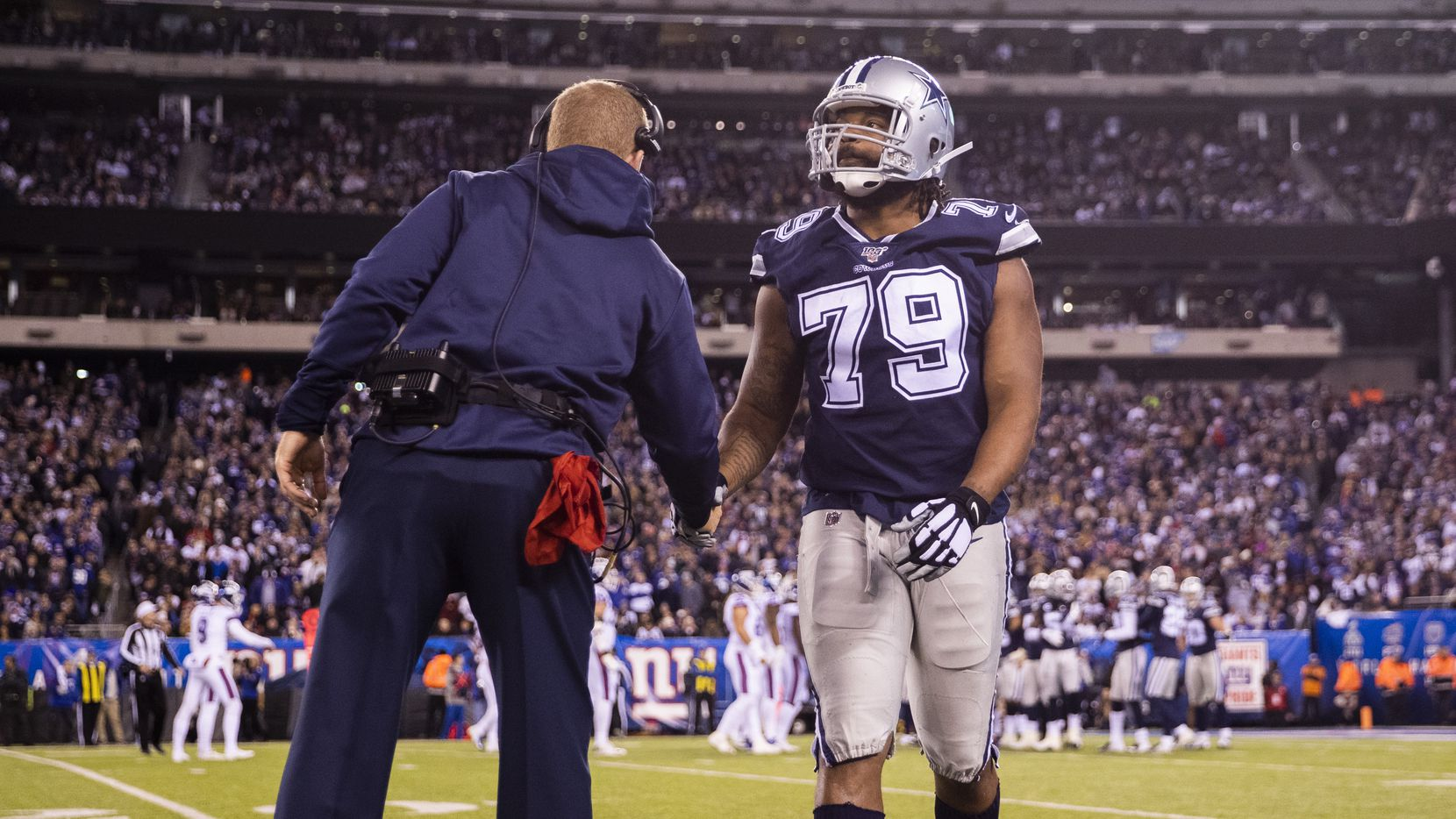 Dallas Cowboys defensive end Michael Bennett (79) gets a high five from Dallas Cowboys head coach Jason Garrett as he walks off the field during the third quarter of an NFL game between the Dallas Cowboys and the New York Giants on Monday, November 4, 2019 at MetLife Stadium in East Rutherford, New Jersey.